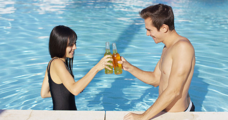 Handsome young couple toasts in swimming pool with bottled beverages on a sunny day