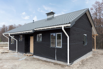 SIP panel house with new gray metal tile roof,white rain gutter and insulation