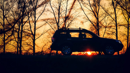 view on the road with silhouette of car and trees during sunset