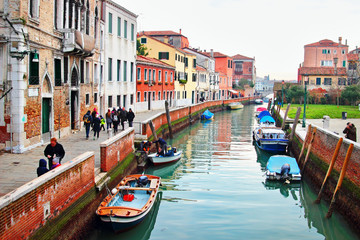 View of the canal and embankment with old historic buildings in Venice, Italy.