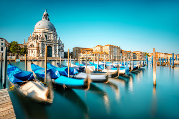 Wall Murals Gondolas Venice cityscape view on Santa Maria della Salute basilica with gondolas on the Grand canal in Venice. Long exposure image technic with motion brured boats