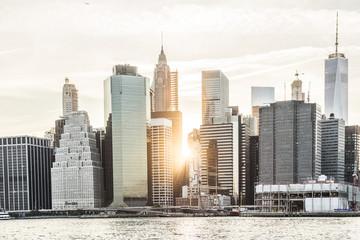 Sunburst between skyscrapers of the Manhattan skyline in New York City during sunset