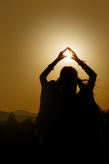 silhouette of woman hands holding sun in triangle on background
