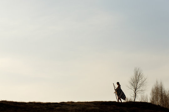 silhouette of native indian american woman walking on hill among
