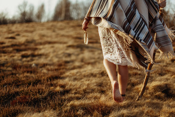 Woman walking in field with traditional blanket