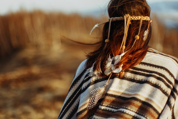 back of native indian american woman walking in mountains in eve