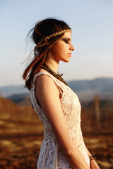beautiful boho woman relaxing in sunny evening on top of a mount