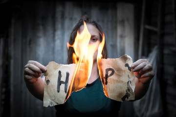 """A girl holding a sheet of paper with the word """"help"""". In the center of the sheet is a fire."""