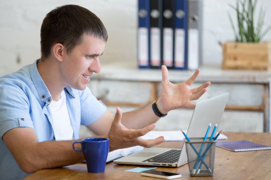 Young stressed businessman sitting with laptop gesticulating with angry and furious expression. Annoyed business man looking at laptop screen, made mistake or irritated by work. Negative human emotion
