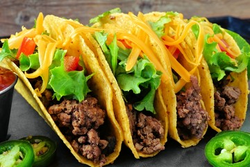 Group of hard shelled tacos with ground beef, lettuce, tomatoes and cheese close up Wall mural