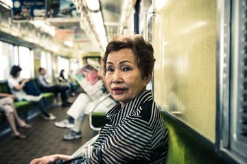電車に乗っている高齢の日本人女性
