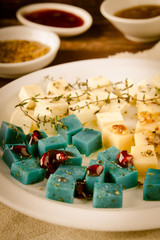 Cheese platter, Gouda, feta, blue pesto cheeses on white plate with herbs, olive oil, pomegranate and mustard sauces