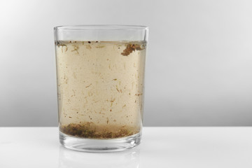 Glass of contaminated water on grey background