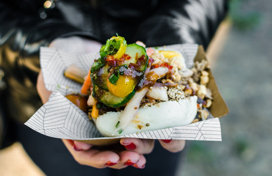 Close up photo of a traditional Vietnamese banh bao steamed bun with pork filling at a street food market. Selective focus.