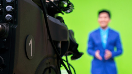 close-up a television camera with presenter out of focus in background