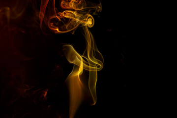Abstract yellow red smoke from aromatic sticks.