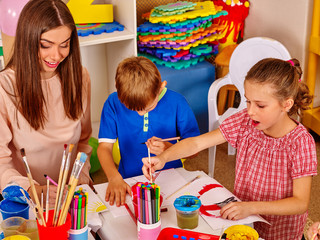 Children with teacher woman painting on paper at table in school. Painting school. Preschool children's development.