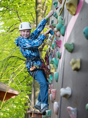 Teenager in helmet and with a safety rope climbing wall holding hooks on the blurred background of trees