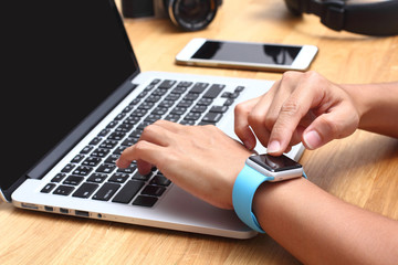 Hands of woman wearing touch screen smartwatch on the keyboard o