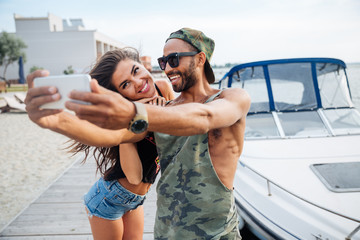 Portrait of a happy couple making selfie photo on smartphone