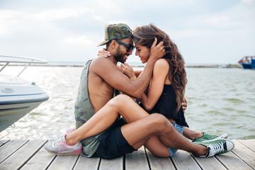 Couple in love sitting and kissing at wooden sea pier