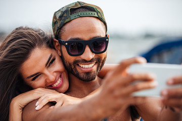 Couple making selfie photo on smartphone at the sea pier