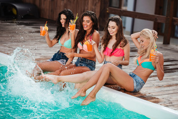 Cheerful young women with cocktails having fun near swimming pool