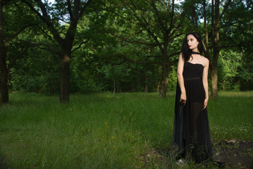 Beautiful brunette woman in black dress and black cloak in the m