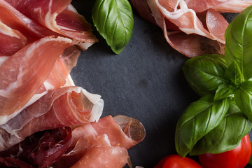 Jamon mix. Ham. Traditional Italian and Spanish salting, smoking, dry-cured dish - jambon Serrano and prosciutto crudo sliced with herbs and tomatoes on dark stone background. Copy space. Closeup.