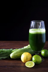 Close up of healthy mixed green vegetable juice on wooden table.