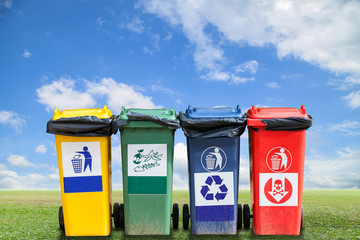 recycle bins and bag garbage on green grass and sky background ,