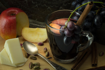Seasoned glass of red wine, with grapes, apple, pieces of vegan cheese, pistachios and cinnamon sticks