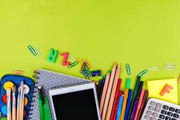 School supplies on green background