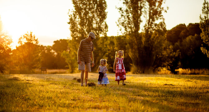 Grandfather walking with his two grandchildren in a park at sunset
