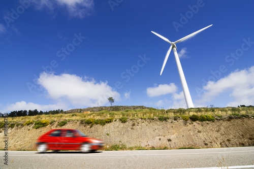 wind turbines with car in motion blur in eolic farm. Black Bedroom Furniture Sets. Home Design Ideas