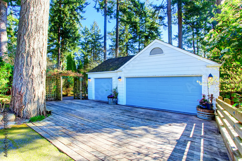 Separate garage with blue door and wooden driveway for Separate garage
