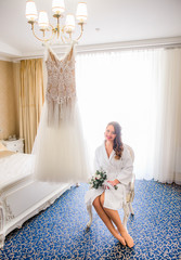 Happy bride sits before shining wedding dress which hangs on the