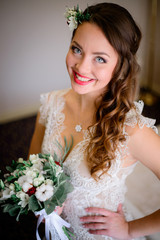 Happy bride with beautiful blue eyes poses in rich hotel room