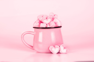 marshmallow heart shape in cup on pink background