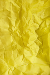 A full page of scrunched up bright yellow wrapping paper texture