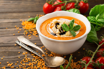 Homemade lentil soup with cream, croutons and basil on dark rustic wooden background