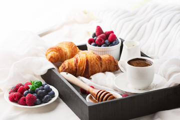 Breakfast in bed with cup coffee and croissants