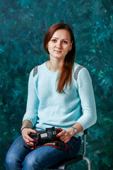 beautiful woman in a turquoise sweater with a photo camera