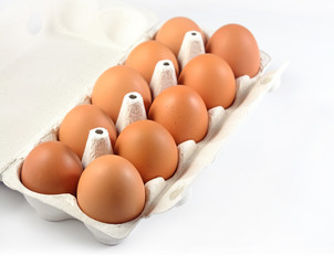 Carton of fresh brown eggs on a white