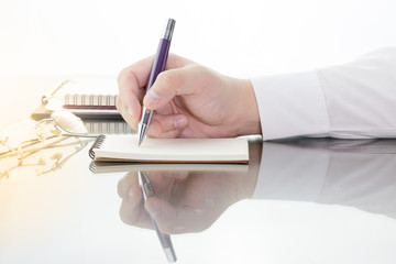 Businessman write a short note on opened notebook with pen and glasses.