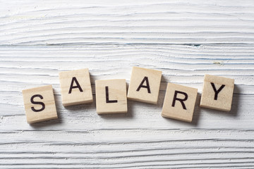 SALARY word written on wood block at wooden background.