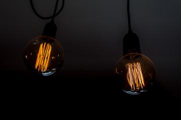 Two round tungsten light bulbs shining in a dark room.