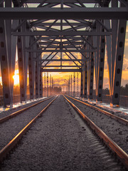 Toned image of the railway with sleepers and rail bridge on a background of multicolored sunset with clouds in the sky