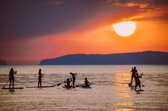 SUP im Sonnenuntergang/Gruppe von SUP`s in der Sonne