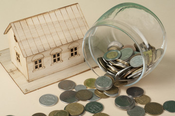 Saving to buy a house, real estate or home savings. Piggy bank, coins and toy model